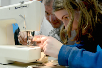 Fixers threading a sewing machine.